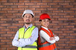 Industrial engineers in uniforms on brick wall background. stock photography
