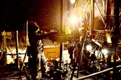 Industrial equipment for oil well overhaul. Night work of oil well workers team Royalty Free Stock Photos