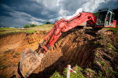 Industrial excavator loading soil from highway construction site Stock Images