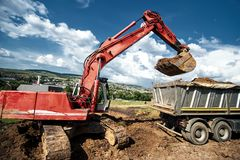Industrial excavator loading soil material from quarry Stock Images