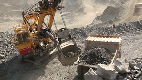 Industrial excavator and working man in a quarry, a large jaded industrial excavator stock video footage