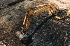 Industrial excavators working on garbage dump. Heavy duty machinery at work Royalty Free Stock Image