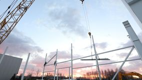 Industrial exterior, Mounting of metal structures against the background of an orange sky with clouds, construction work. Construction of an industrial stock video footage
