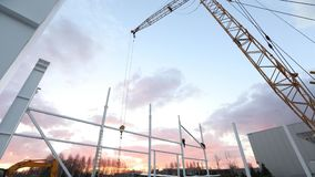 Industrial exterior, Mounting of metal structures against the background of an orange sky with clouds, construction work. Construction of an industrial stock footage