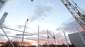 Industrial exterior, Mounting of metal structures against the background of an orange sky with clouds, construction work. Construction of an industrial stock video
