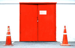 Industrial exterior red door with traffic cone Stock Image
