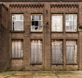 Industrial facade. Brick facade of an old and grungy building with broken windows and boarding Royalty Free Stock Image