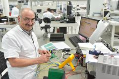 Industrial factory for assembly of microelectronics - older, fri. Endly worker at the workplace stock photo