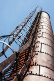 Industrial factory chimney against blue sky Stock Photos