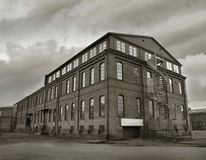 Industrial Factory Depression. Old depressing factory building in sepia tone. Symbol for economic depressions royalty free stock photos