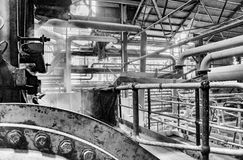 Industrial factory interior. Part of the inside of old gritty grungy factory mill showing steam pipes and machinery Stock Photography
