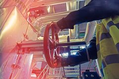 Industrial factory worker turning red wheel valve Stock Image