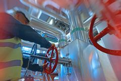Industrial factory worker turning red wheel of valve. Inside power plant royalty free stock photography