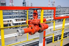 Industrial fire hydrant aimed at the technological equipment of the refinery stock photography