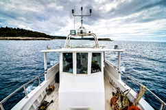 Industrial fishing boat ship on the sea with dramatic clouds. Stock Images