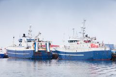 Industrial fishing ships. Blue white trawlers stock photo