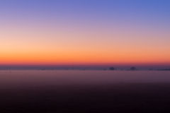 Industrial foggy landscape, silhouette of old factory against the sunset sky and the mist at blue hour at night Royalty Free Stock Image