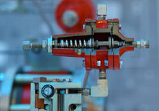 Industrial gas pressure regulator, red color, blue background Stock Photos