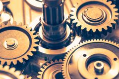 Industrial gear wheels. Golden tone, close-up view Stock Images