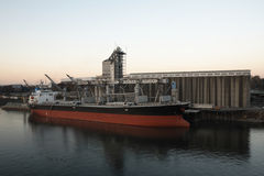 Industrial grain cargo ship and terminal. Industrial waterway with grain cargo ship and elevator terminal exchange at sunset stock image