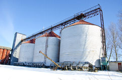 Industrial grain silos construction in winter time Stock Photos