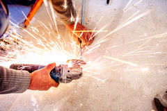 Industrial handyman worker cutting steel with metal grinder Stock Photography