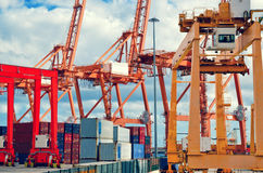 Industrial harbor, gantry cranes and container ship. Red and orange industrial cranes in port of Santa Cruz de Tenerife. Stock Photography