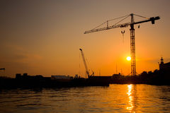 Industrial harbor at sunset and a crane Royalty Free Stock Photography