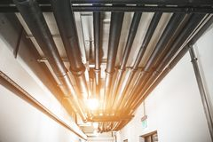 Industrial heating pipes under celling or another household communications pipelines in modern building stock photo