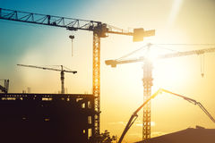 Industrial heavy duty construction site with tower cranes and building silhouettes. Industrial construction site with tower cranes and building silhouettes Stock Images