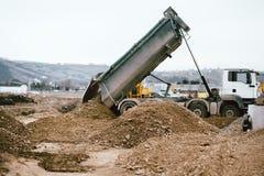 Industrial heavy duty dumper truck unloading gravel for leveling. Heavy duty dumper truck unloading gravel for leveling Stock Image