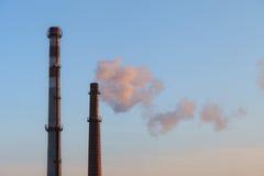 Industrial high chimneys producing smoke Stock Image