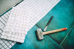 Industrial home construction - Hammer and mosaic, white marble stone ceramic tiles Royalty Free Stock Photos
