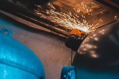 Industrial hvac repair installation worker process. Man repairing the air duct with the angle grinder. Toned photography industrial hvac installation worker royalty free stock images