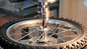 Industrial iron drill in action. Industrial iron drill works on bicycle wheel stock footage