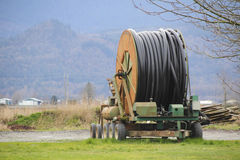 Industrial Irrigation Hose Line and Reel. A large spool on wheels houses an irrigation hose used for watering farm crops Royalty Free Stock Photos