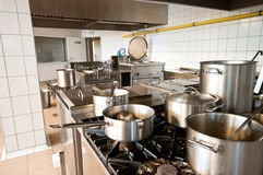 Industrial kitchen. Interior of an industrial kitchen with big stoves and pans, cauldrons Royalty Free Stock Photography