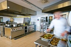 Industrial kitchen interior with busy cooks royalty free stock photography