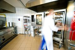 Industrial kitchen interior with busy cooks stock images