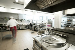 Industrial kitchen. View with busy cooks in motion blur royalty free stock photography