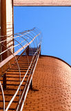 Industrial ladder, blue sky and brick walls of the building Stock Photo