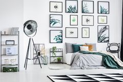 Industrial lamp in modern bedroom. Industrial lamp near king-size bed with green blanket in modern bedroom with gallery of botanic posters stock photography