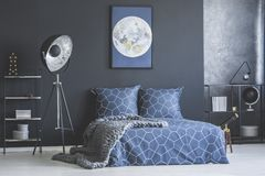 Moon poster in bedroom interior. Industrial lamp next to bed with navy blue bedding against dark wall with moon poster in bedroom interior Royalty Free Stock Photos