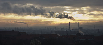 Industrial landscape. Smoke billowing over a dark industrial landscape stock photos