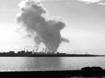 Industrial landscape along the coast. Air polluting factory chimneys . Black and white photo Stock Photos