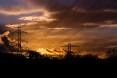 Industrial landscape with cables in front of sunset. Electricity cables and pylons are silhouetted in front of a sunset in Somerset, UK royalty free stock image