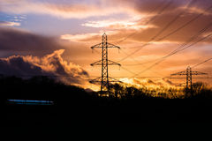 Industrial landscape with cables, train and sunset. Electricity cables and pylons are silhouetted in front of a sunset in Somerset, UK, whilst a train passes royalty free stock image