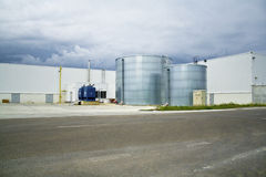 Industrial landscape with cisterns. Two metal cisterns in factory environment Royalty Free Stock Photo