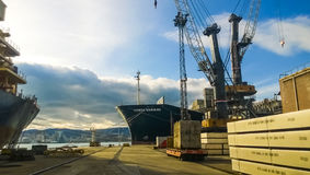Industrial landscape of developed seaport infrastructure. Port cranes and vessels, warehouses and docks Stock Images