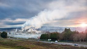 Industrial landscape. Factory smoke rising at sunrise, polluting the atmosphere royalty free stock photography